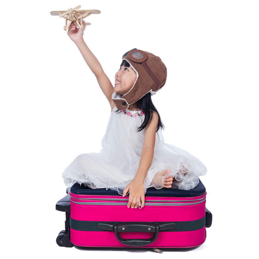 girl sitting on a suitcase with an airplane
